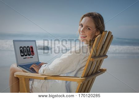 Pretty girl using laptop with 2017 on it at the beach