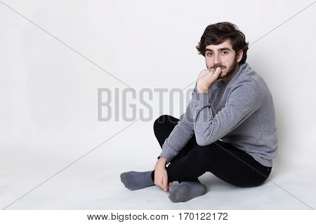 A portrait of handsome man having dark beard with moustache wearing casual clothes sitting on the floor crossed legs holding his hand on his chin looking into camera with mysterious look