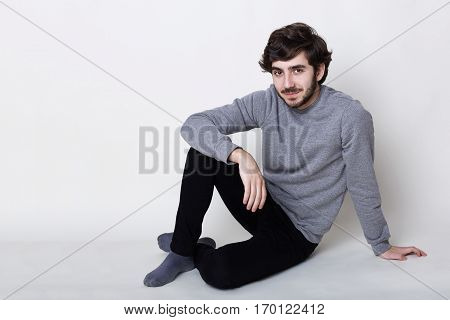 Good-looking pleased hazel-eyed boy with dark beard and moustache thick black eyebrows and stylish hairstyle wearing casual clothes sitting on the floor relaxing indoors having confident expression