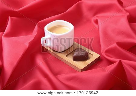 White cup of coffee and cognac in a glasses, pralines on red background