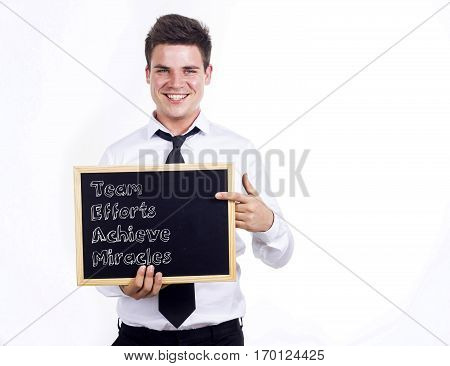 Team Efforts Achieve Miracles - Young Smiling Businessman Holding Chalkboard With Text
