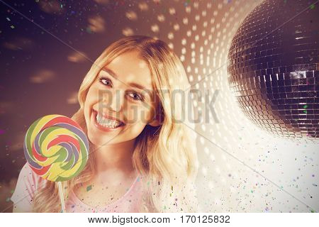 A beautiful woman holding a giant lollipop against shiny disco ball