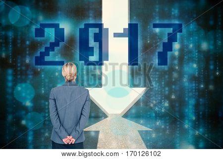 Businesswoman standing with hands behind back against grey room with arrow door