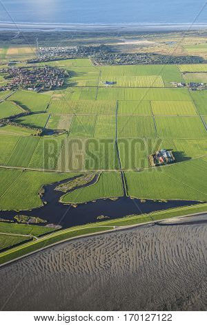 Aerial coastal view of the shore of Ameland Frisian Island with green fields villages a dike and sea The Netherlands