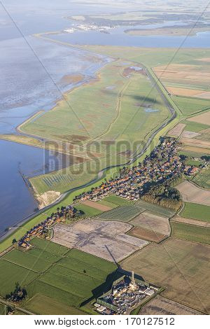 Aerial coastal view of the shore of Ameland Frisian Island with green fields a village dike and sea The Netherlands