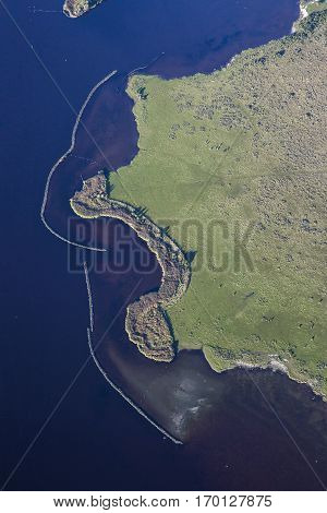 Aerial coastal view of the shore of Ameland Frisian Island with green fields dyke and sea The Netherlands