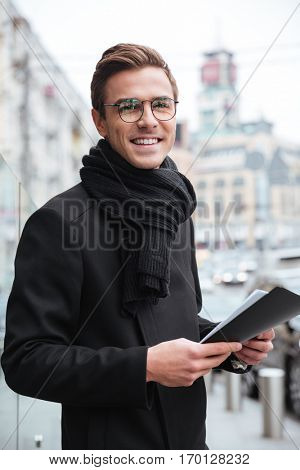 Business man on the street looking at camera. vertical image. smiling man
