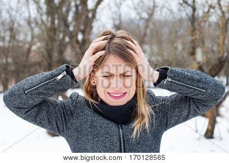 Picture of a young female having a bad headache outdoor