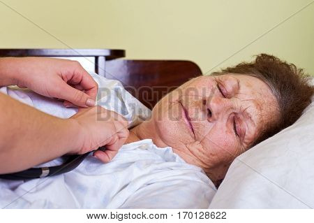 Picture of a bed ridden elderly woman with her carer