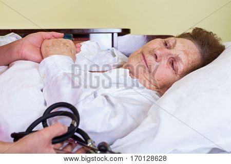 Picture of an elderly woman having fever lying in bed