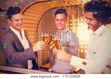Group of friends toasting a glass of beer against flying colours