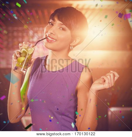 Young woman dancing on dance floor while having cocktail against flying colours