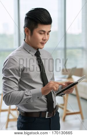 Concentrated Asian businessman standing in office against panoramic window while surfing the net on his digital tablet