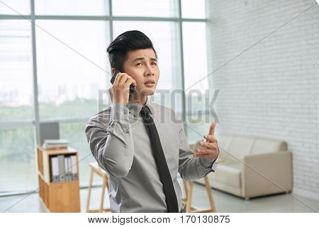 Handsome young businessman discussing project with his colleague on smartphone and gesticulating against panoramic window of office lobby