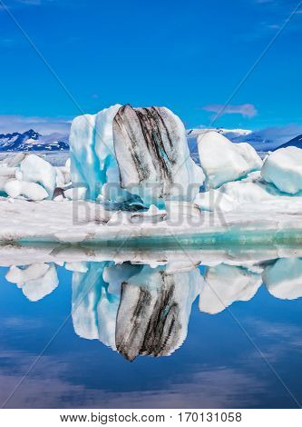 Ice lagoon in July.  Ice floes and icebergs are reflected in the mirrored water of ocean. Summer in Iceland