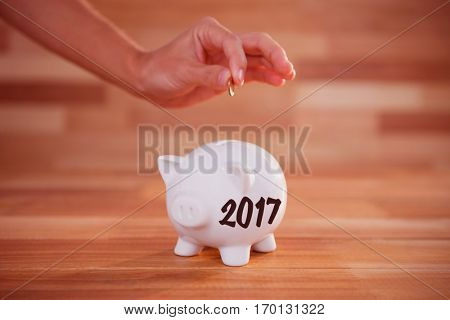 Digital image of new year 2017 against cropped image of hand inserting coin in piggy bank