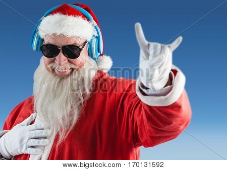 Cheerful Santa claus listening music on headphones and gesturing