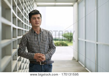 Portrait of confident young employee in checked shirt standing in office patio and looking away seriously