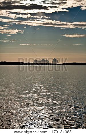 Midnight sun Norwegian Landscape with and oil sea and the mountain shape of Traena Island