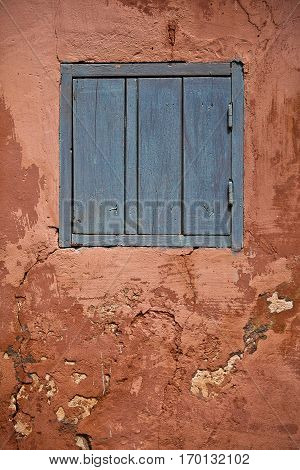 closed blue wooden shutters and ocher decrepit wall