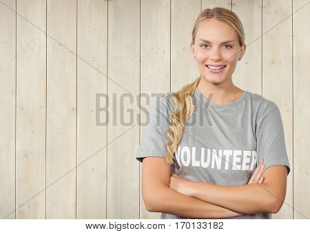 Portrait of confident female volunteer standing with arms crossed against wooden background