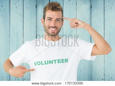 Portrait of smiling man in volunteer tshirt pointing at head against wooden background