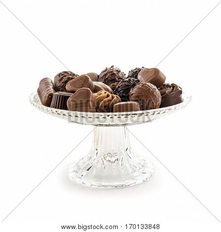 Chocolate praline assortment on an elegant glass serving plate isolated with shadows against a white background selected focus narrow depth of field