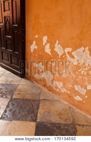 Old ocre decay wall and vintage tiled floor
