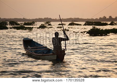 silhouette of a fisherman in the sunset Senegal Saloum delta