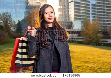 Asian woman holding shopping bags in hand standing in outdoors over a skyscraper in sunlight. Walking on the grass posing smiling after shopping