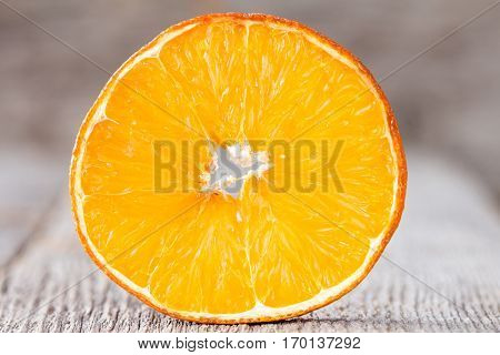 Cross section of orange fruitclose up on wooden background