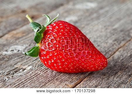 One fresh big red strawberry on a wooden table