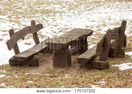 Wooden picnic table with benches in the winter park