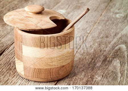 Wooden bowl with a spoon for condiment and sauce