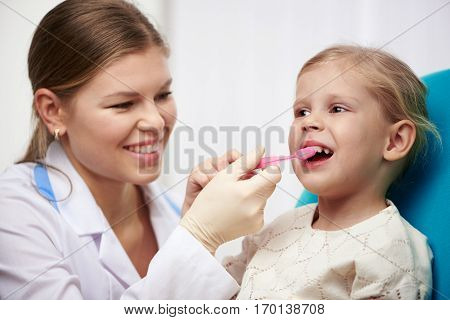 Happy girl learning to brushing teeth in dentist office. Young woman doctor holding toothbrush, teaching oral hygiene little child.