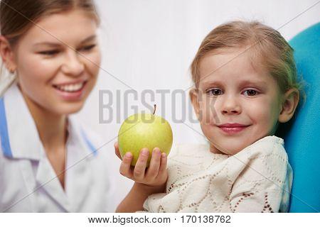 Milk teeth inspection. Smiling girl holding apple in dentist office.