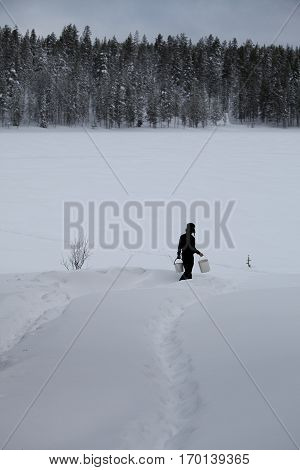 Winter Finnish snowy landscape with a man walking in the snow to fetch water from frozen lake