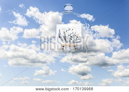 Surrealistic image of blue cheese covered by transparent French cheese glass bell floating in the blue sky among fluffy clouds