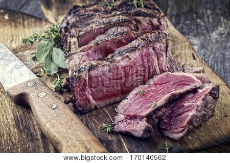 Barbecue Rib Eye Steak sliced on Cutting Board