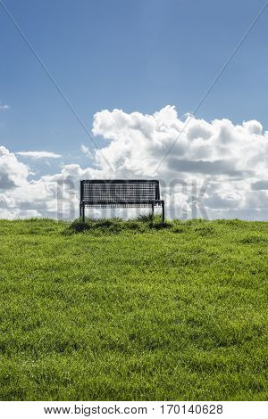isolated public bench on the top of a dyke with green grass blue sky and white cloud