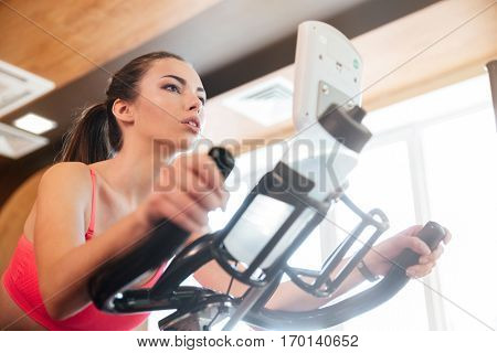 Focused pretty young sportswoman exercising on bicycle in gym