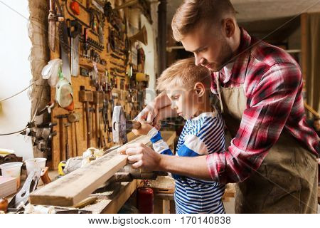 family, carpentry, woodwork and people concept - father and little son with hammer hammering nail into wood plank at workshop poster