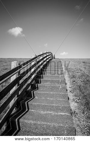 Black and white view of concrete staircase with wood banister between the green grass of a dike on a sunny day