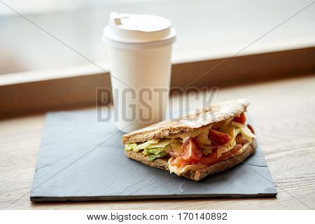 food, dinner and eating concept - salmon panini sandwich with tomatoes and cheese on stone plate and cup of drink on cafe table