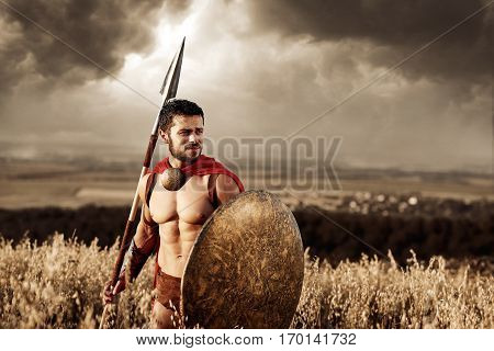 Confident and athletic soldier in red cloak wearing like spartan holding iron weapon in hand. Brunet warrior with bare torso going in attack with rounded shield and weapon. War in field.