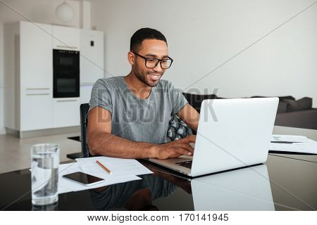 Photo of happy african man dressed in gey t-shirt and wearing eyeglasses using laptop and sitting at the table.