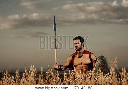 Athletic warrior with beard wearing like spartan among grass in field, holding iron weapon. Brunet soldier with bare torso in red cloack going in attack with rounded shield and weapon. Gray sky.