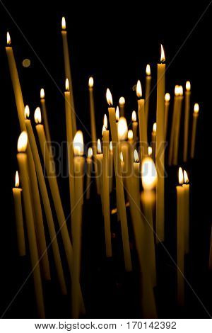 Burning candles in a church with black background