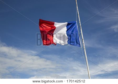 Flag of France floating and flapping in the wind in front of a blue sky background