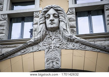 Detail of the Art Nouveau building facade with a carved head in Old Town Riga Latvia